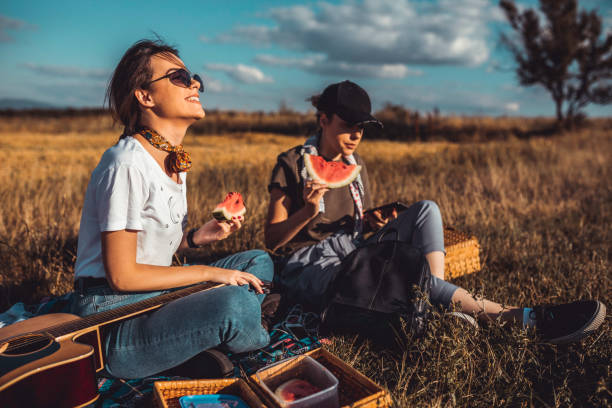 Sisters eating watermelon during a picnic on a sunny day stock photo