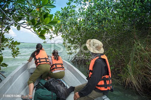 Adventure and eco-tour guide and tourists in motor boat exiting mangrove river channel and entering open ocean.  Sian Ka-an Biosphere Reserve.  Tulum, Quintana Roo, Yucatan Peninsula, Mexico.