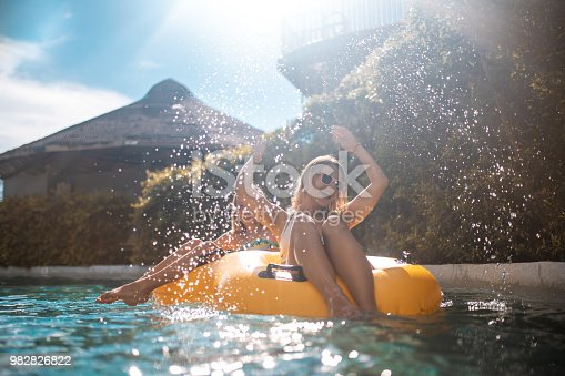 Smiling sisters relaxing on yellow inflatable ring at water park. They are floating in swimming pol. They are enjoying summer vacation.