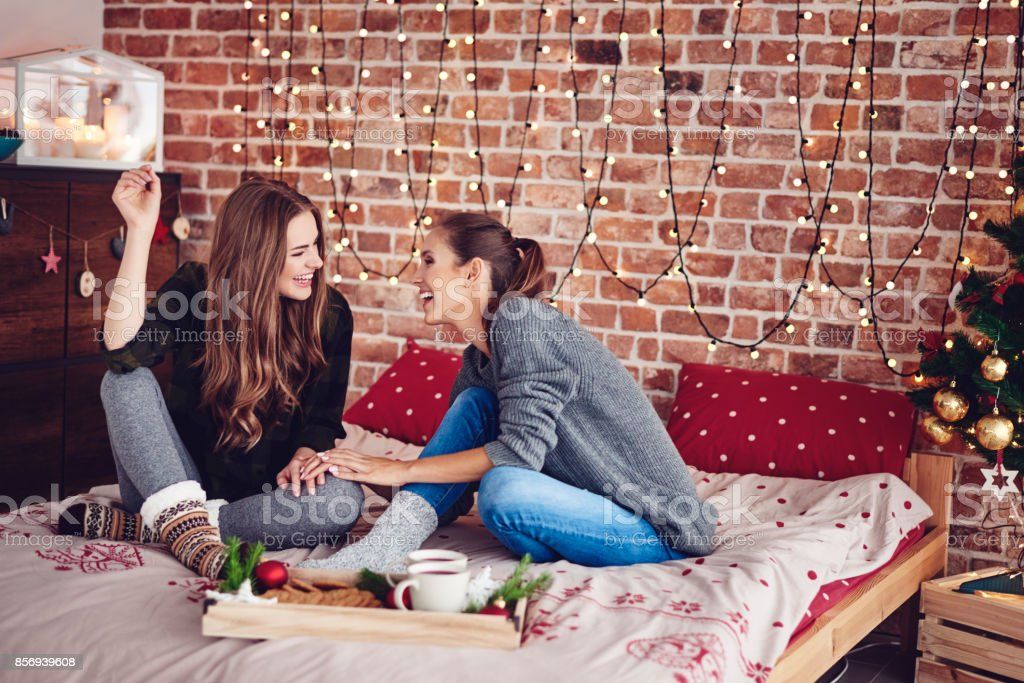 Sisters gossiping and laughing in bedroom stock photo
