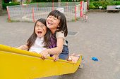 Two sisters are happily enjoying their time together in a public park.