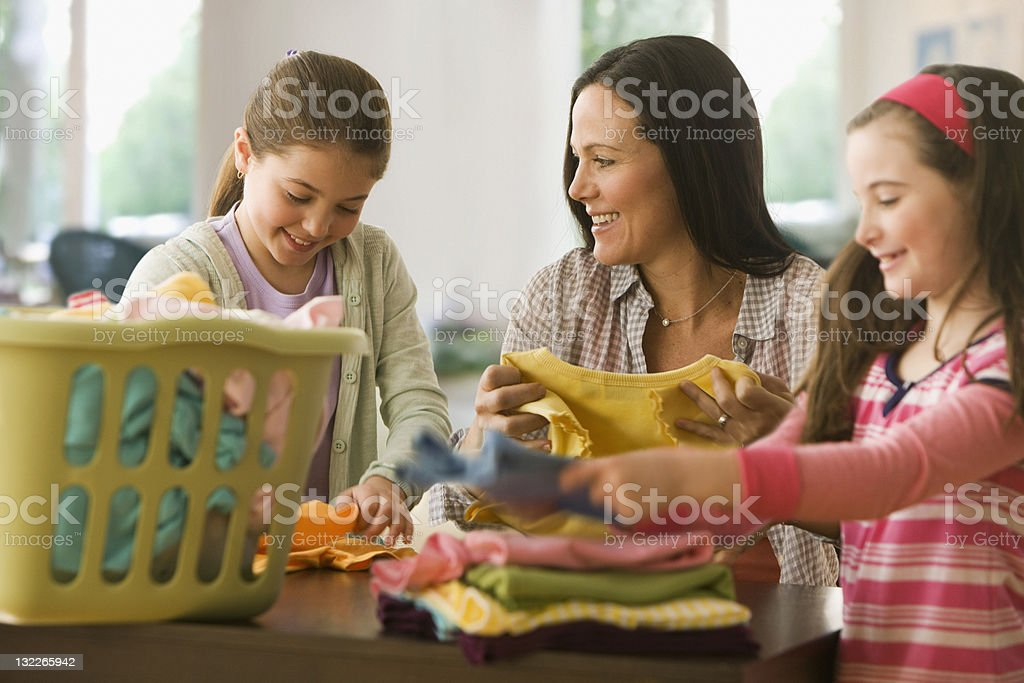 Sisters helping mother with laundry stock photo