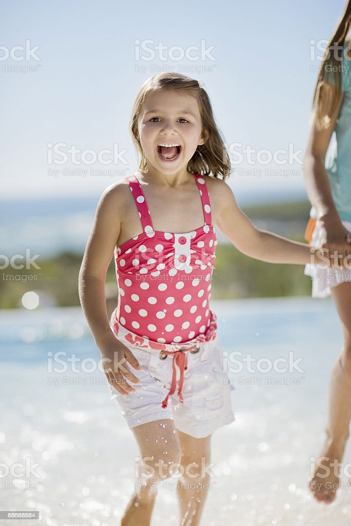 Sisters holding hands and wading in water royalty-free stock photo