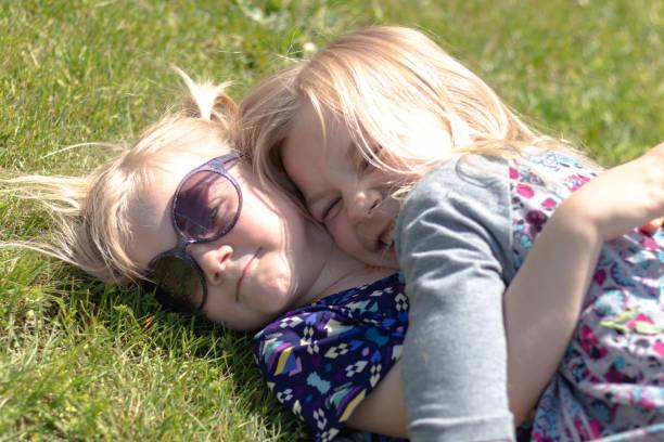 Sisters Hugging in the Grass 1 – zdjęcie