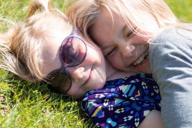 Sisters Hugging in the Grass 2 – zdjęcie