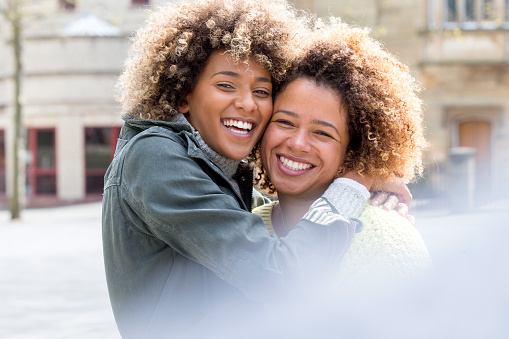 Two friends hugging and smiling for the camera in the city.