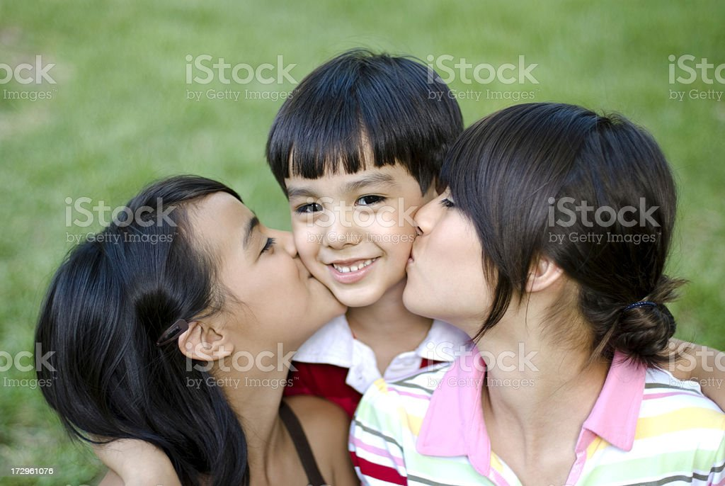 sisters kissing his little brother royalty-free stock photo