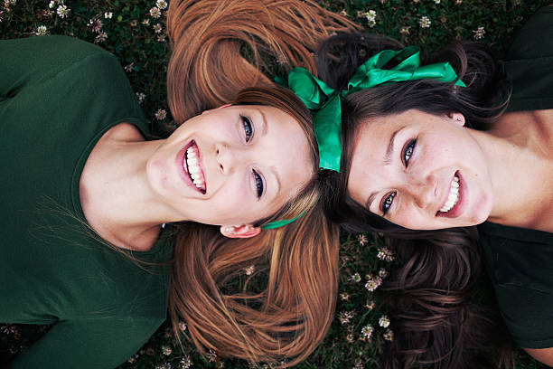 sisters laughing and laying down - st patricks day stock photos and pictures