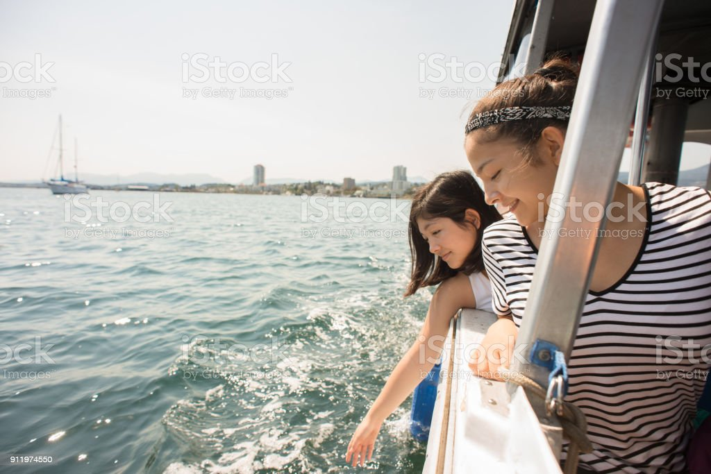 Sisters Lean, Reach Out to Touch Water on Boat Ride_WF.jpg stock photo