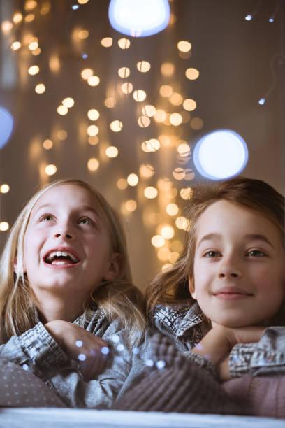 schwestern, schaut aus dem fenster - weihnachten 7 jährige stock-fotos und bilder