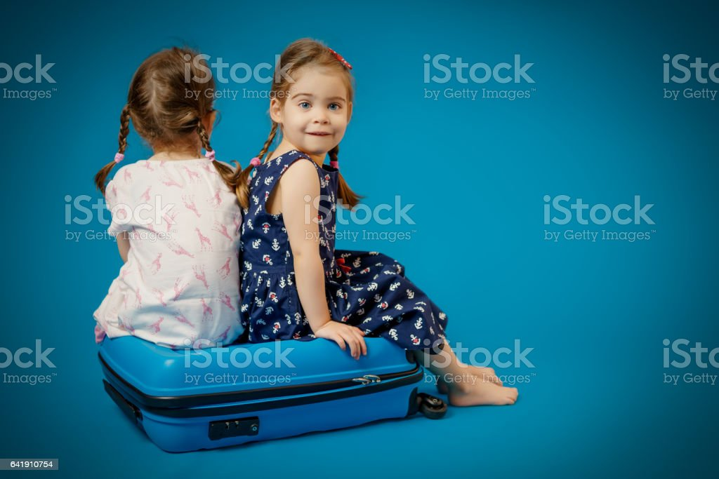 sisters on a suitcase waiting for trip stock photo