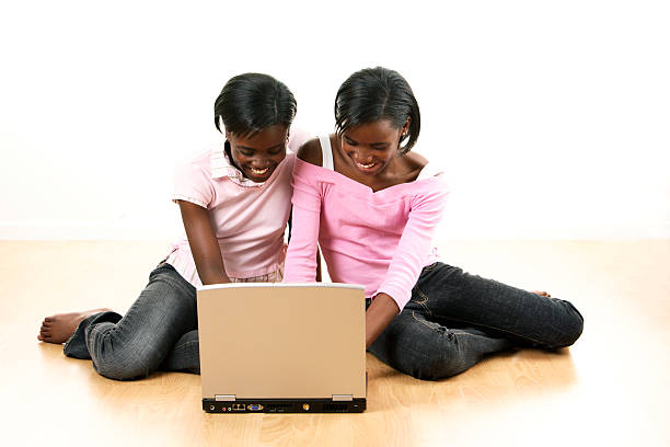Sisters on laptop 2 stock photo