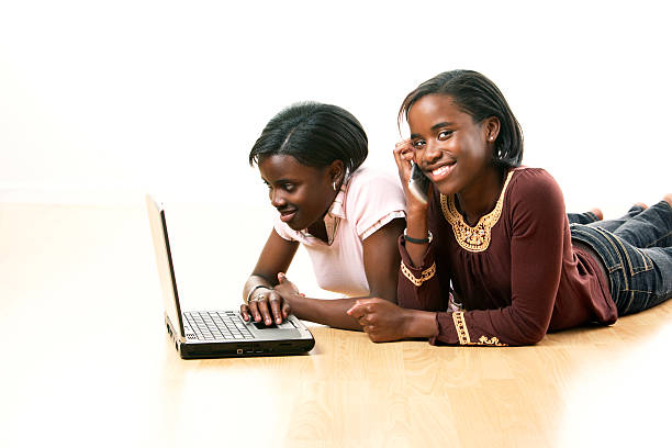 Sisters on laptop stock photo