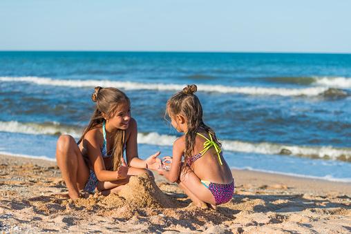 Sisters play near the sea
