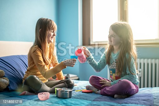 Sisters playing on bed during lockdown quarantine