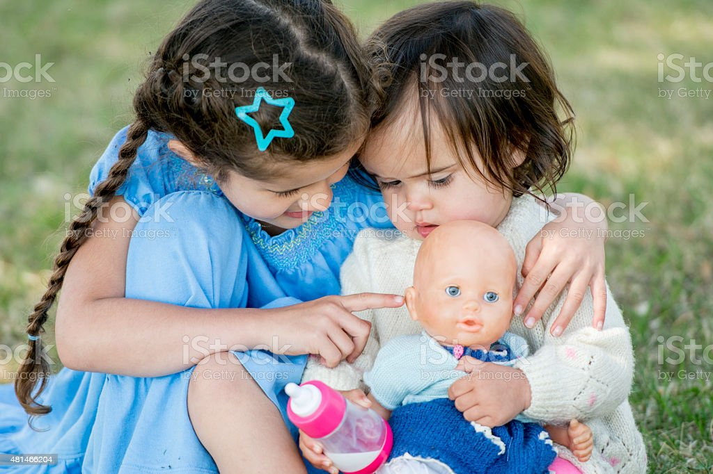 Sisters Playing with Doll stock photo