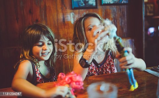 Two girls at a restaurant booth table play with Plastic dolls in a candid photo of childhood friendship and imagination