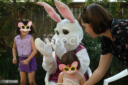 female sisters 3-5 posing with the Easter Bunny during a easter family celebration in the backyard.