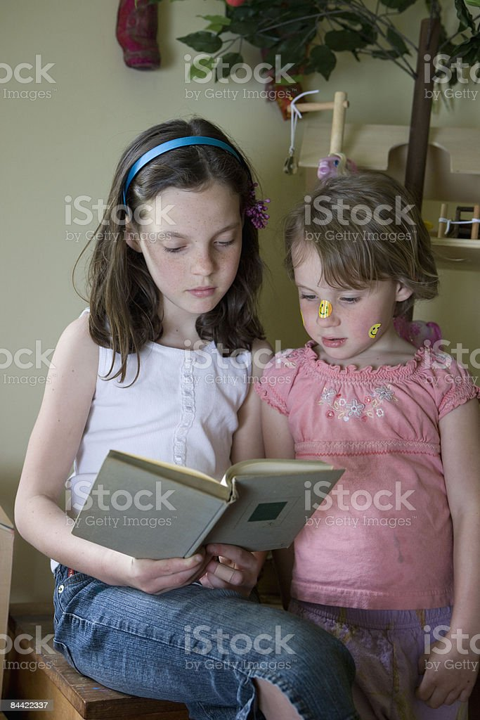 Sisters reading book in playroom royalty-free stock photo