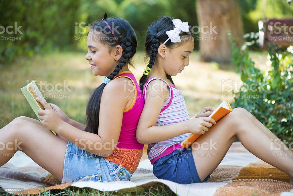 Sisters reading book in summer park stock photo