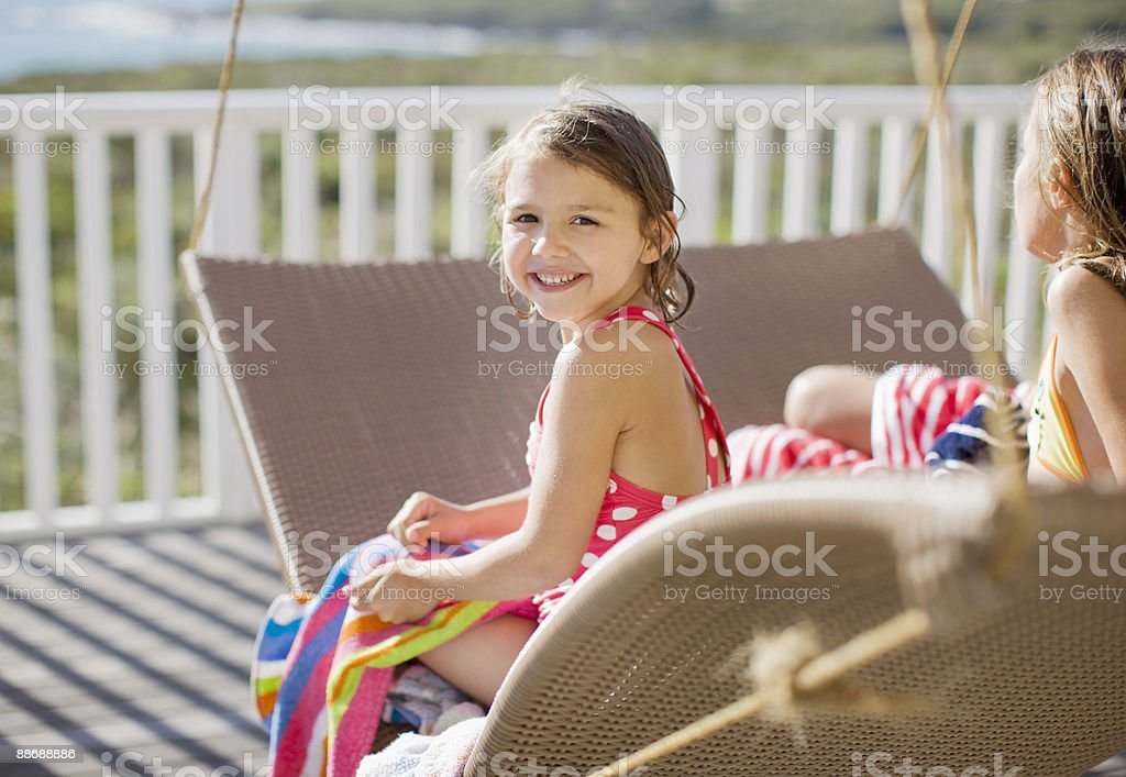 sisters relaxing on lounge chair on deck royalty-free stock photo