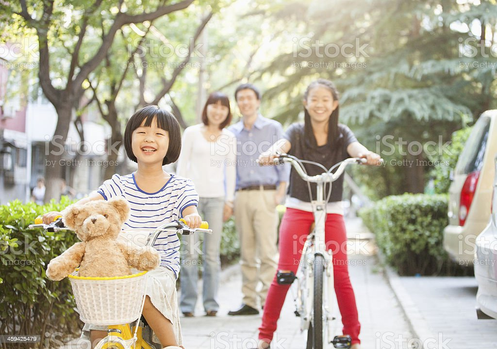 Sisters riding their bikes with parents watching stock photo
