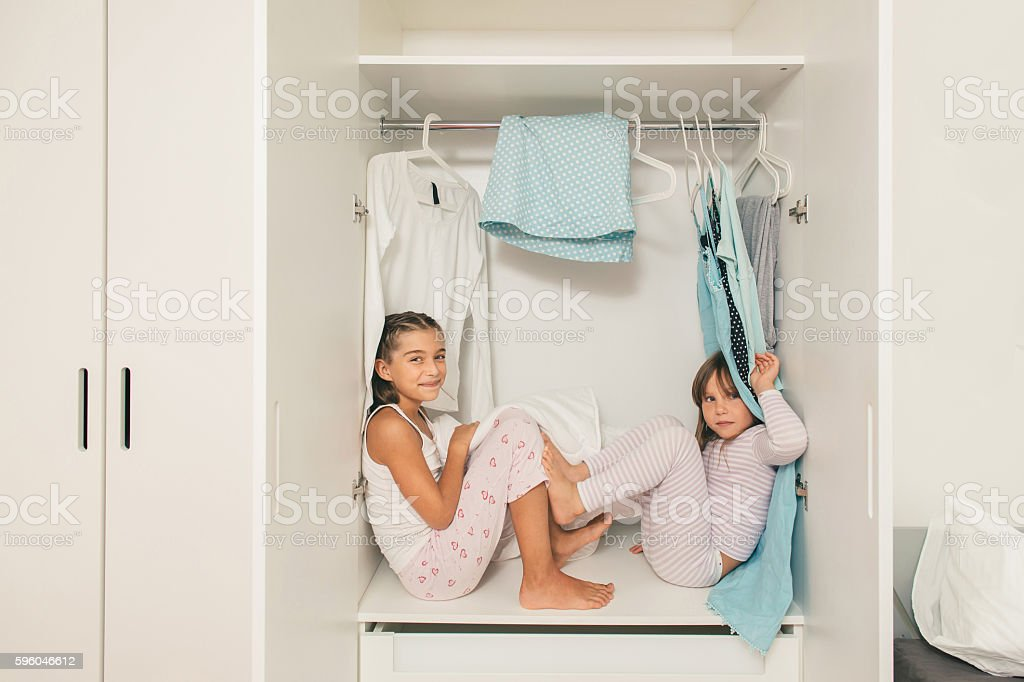 Sisters sitting and playing in wardrobe stock photo