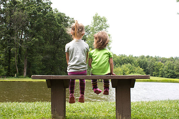 Sisters sitting on a bench at a pond stock photo