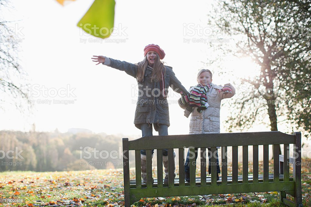 Sisters Standing on bench outdoors in autumn royalty-free stock photo