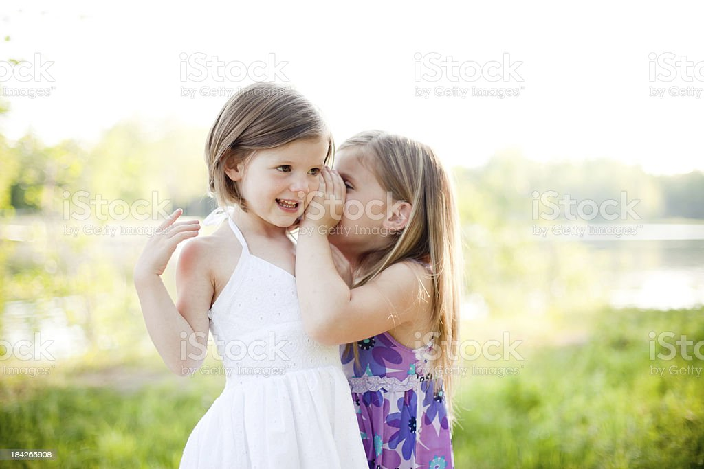 Sisters telling secrets royalty-free stock photo