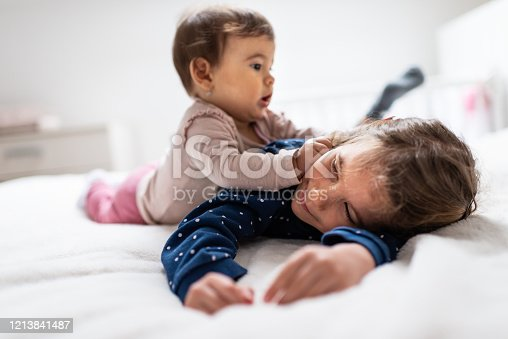 Happy baby is lying down with her older sister on the bed in bedroom. They are playing together.