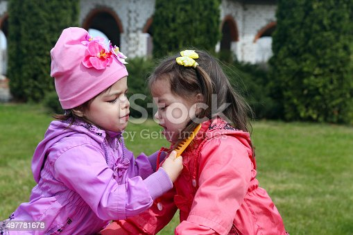 Sisters-twins comb each other.