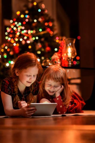 schwestern mit tablet-pc am boden während der weihnachtszeit - kinder weihnachtsfilme stock-fotos und bilder