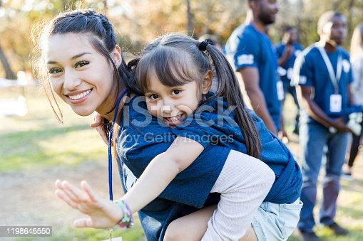 Young girl rides piggyback on her big sister's back during a community cleanup event. They are smiling at the camera.
