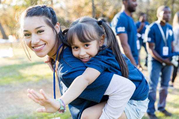 Sisters volunteering together Young girl rides piggyback on her big sister's back during a community cleanup event. They are smiling at the camera. social responsibility stock pictures, royalty-free photos & images