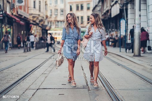 Smiling twin sisters walking on the street