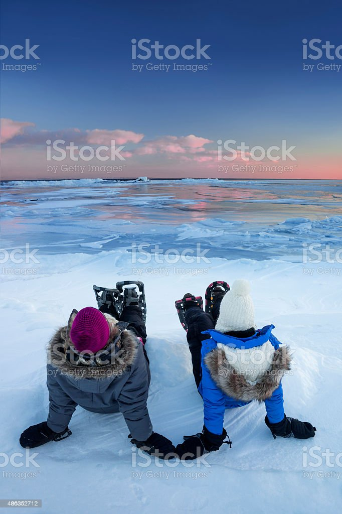 Sisters watch sunset while snowshoeing stock photo