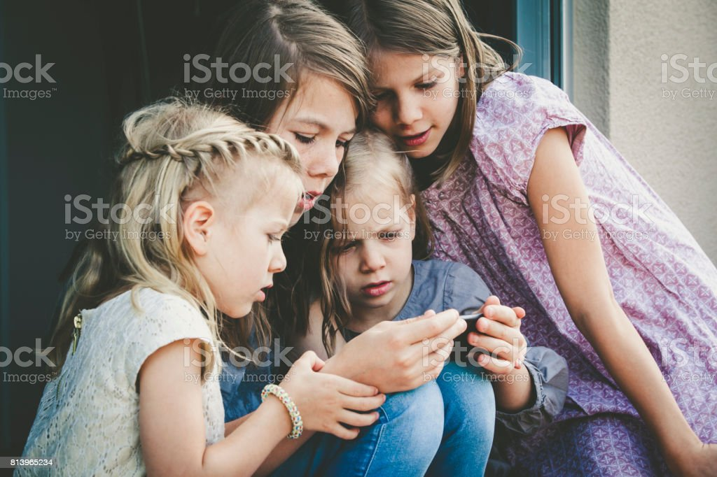 sisters watching on mobile phone stock photo