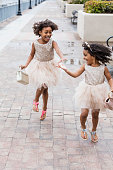 Sisters wearing dresses, playing in rain puddles