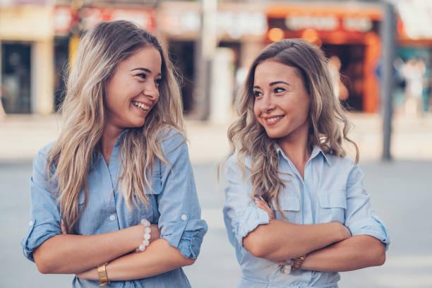 schwestern mit verschränkten armen sahen einander - zwillinge stock-fotos und bilder