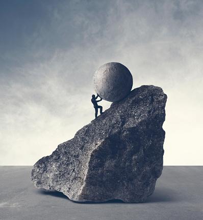Man pushing huge concrete ball up hill. Sisyphus metaphor.