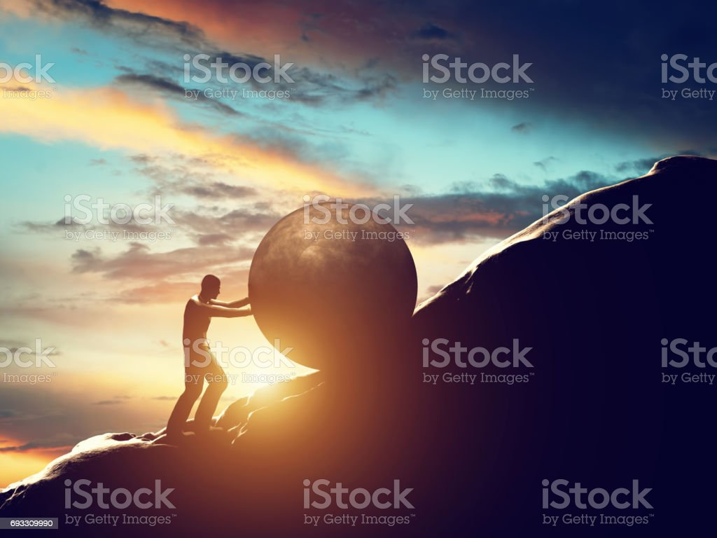 Sisyphus metaphor. Man rolling huge concrete ball up hill. stock photo