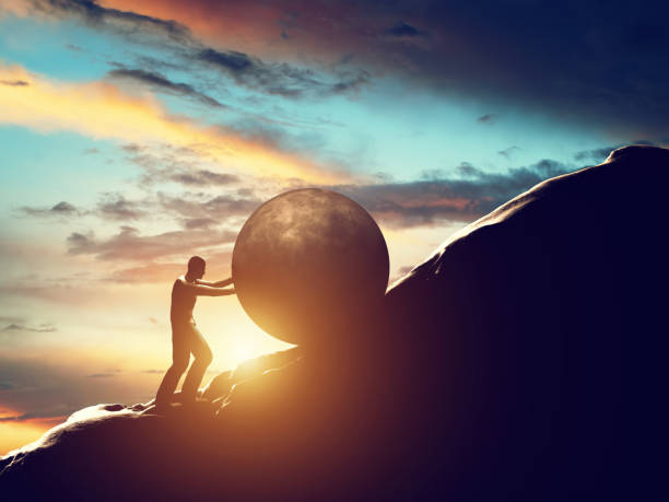 sisyphus metaphor. man rolling huge concrete ball up hill. - penedo imagens e fotografias de stock