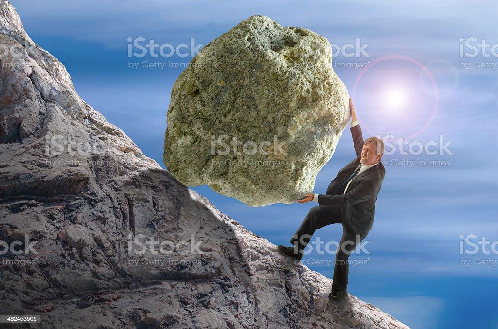 Sisyphus metaphor man rolling huge rock ball up hill stock photo