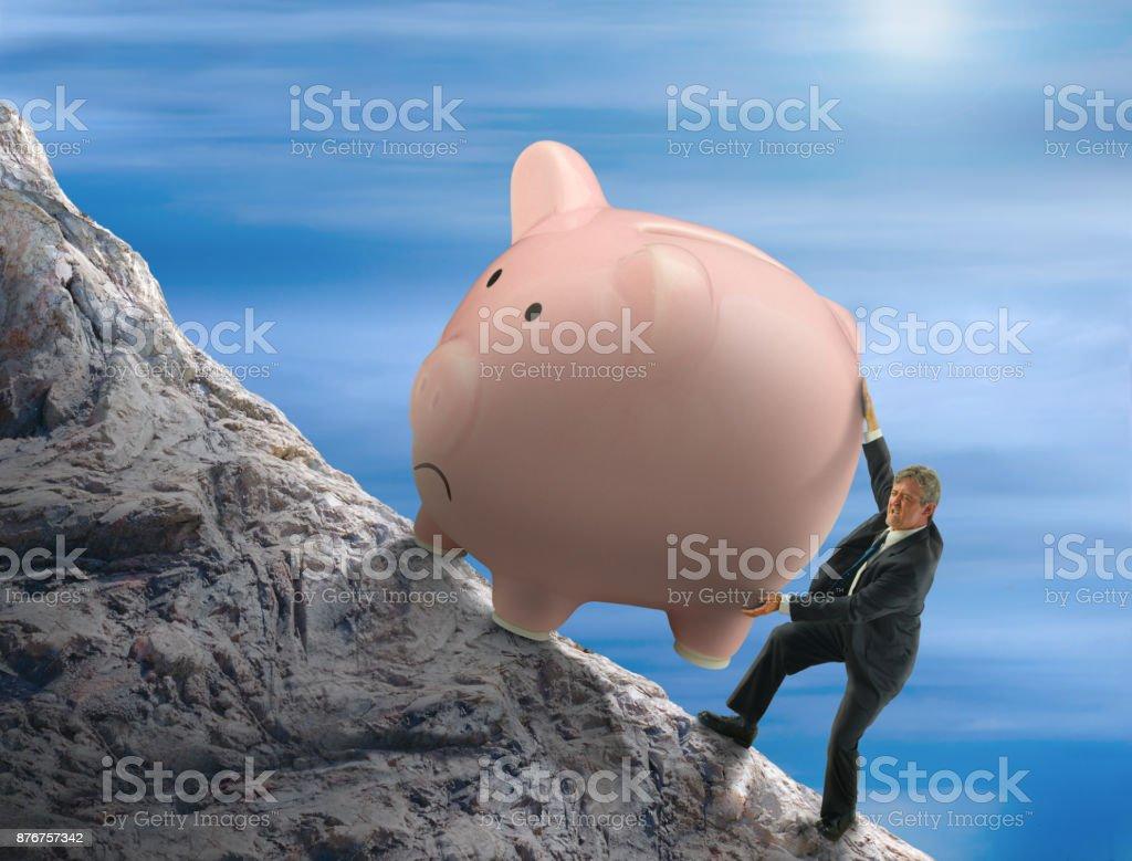 Sisyphus metaphor man trying to push giant piggy bank up a mountain stock photo