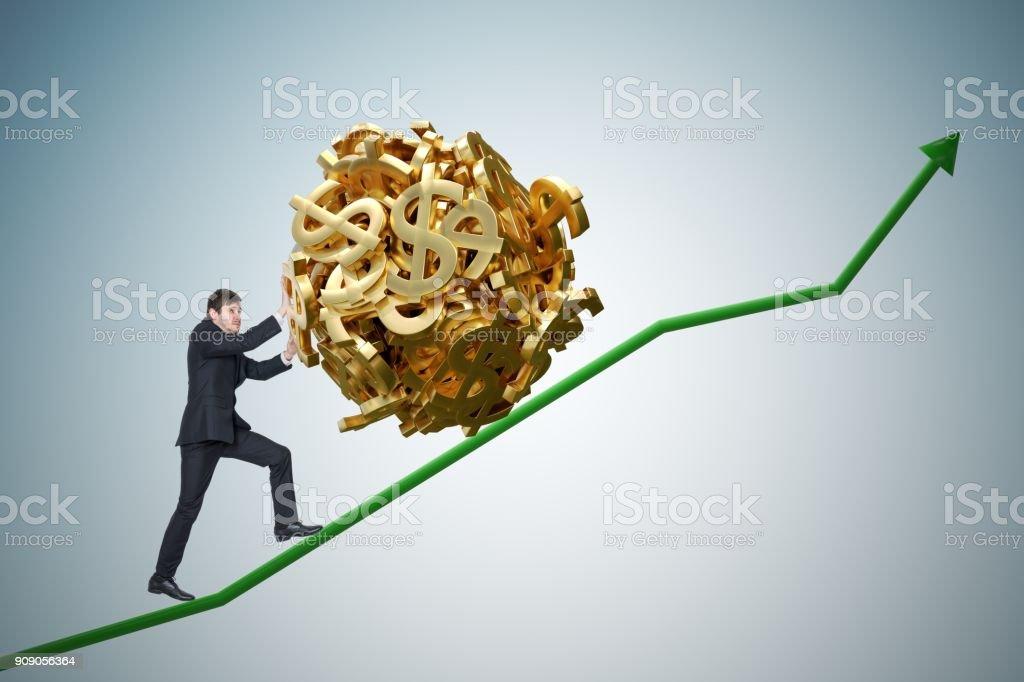 Sisyphus metaphore. Young businessman is maximizing earnings and pushing heavy boulder made of dollar symbol up on chart. stock photo