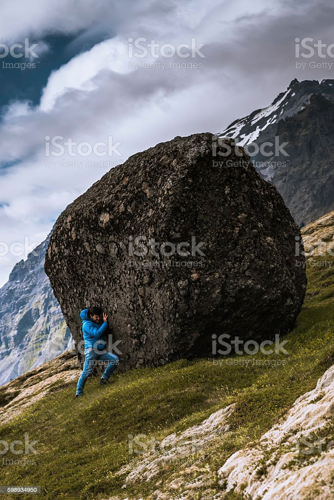 Sisyphus puhing a boulder up the hill stock photo
