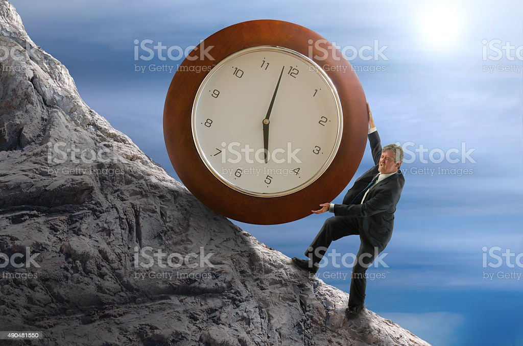 Sisyphus stressed for time man rolling huge clock up hill stock photo