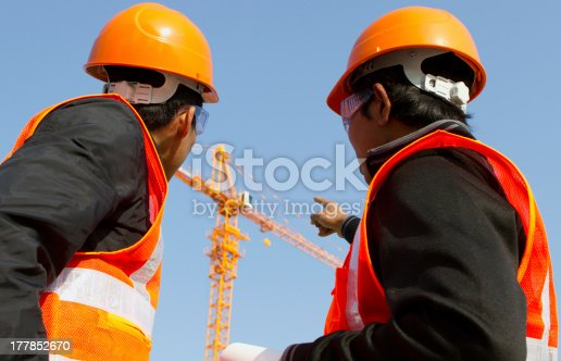 istock Site manager with safety vest discussion under construction 177852670