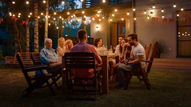 siedząc przy stole przystojny młody człowiek gra na gitarze dla przyjaciół. rodzina i przyjaciele słuchanie muzyki na summer evening garden party celebration. - zmrok zdjęcia i obrazy z banku zdjęć